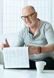 Portrait of senior man with newspaper Stock Photo