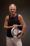 Portrait of a senior man posing with a weighing scale Stock Photo