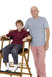 Portrait of senior man with pre-teen boy sitting on director's chair over white background Royalty Free Stock Photos