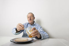 Portrait of senior man preparing slice of bread and marmalade at table Stock Photo