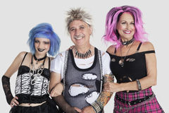 Portrait of senior man with punk females over gray background Royalty Free Stock Photo