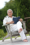 Portrait of senior man reading book on terrace Royalty Free Stock Photography