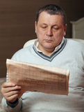 Portrait of senior man reading newspaper at home. Royalty Free Stock Image