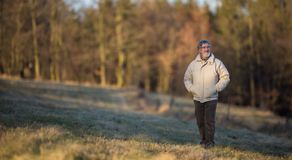 Portrait of a senior man relaxing during a walk outdoors. On a sunny winter day Stock Photography