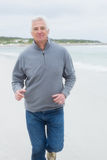 Portrait of a senior man running at beach Stock Photos