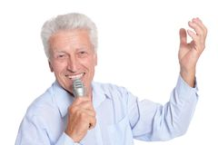 Portrait of senior man singing karaoke. Isolated on white background Stock Images