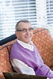 Portrait of senior man sitting on living room sofa Stock Image