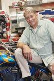 Portrait of senior man sitting on motorcycle in workshop Royalty Free Stock Photos