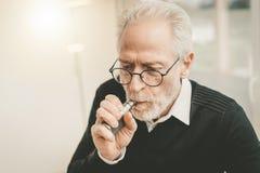 Senior man smoking electronic cigarette stock images