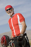 Portrait Of A Senior Man Standing By Bicycle Royalty Free Stock Photo