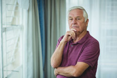 Portrait of senior man standing with hand on chin Royalty Free Stock Image