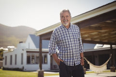 Portrait of senior man standing with hand on pocket outside his house Royalty Free Stock Photo