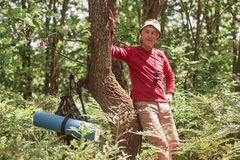 Portrait of senior man standing near tree over forest background. Mature man with rucksack and rug stops to have rest after long. Hours backpacking. Traveling royalty free stock image
