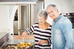 Portrait of senior man standing with wife cooking food. Portrait of senior men standing with wife cooking food at counter Royalty Free Stock Photo