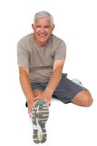 Portrait of a senior man stretching hands to leg Royalty Free Stock Photos