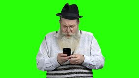 Portrait of senior man surfing internet on mobile phone. Surprised old man looking at his smartphone on green screen. Seniors and modern technology concept stock footage