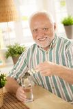 Portrait of senior man taking medicine at home. Smiling at camera, holding bubble package Royalty Free Stock Images
