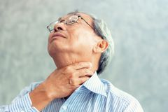 Portrait of senior man touching his neck and having throat irrit. Ation Stock Photo