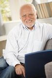 Portrait of senior man using computer on sofa Royalty Free Stock Photography