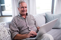 Portrait of senior man using laptop in living room Royalty Free Stock Photography