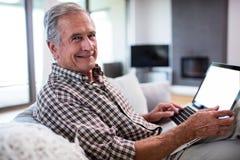 Portrait of senior man using laptop in living room Stock Image