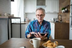 Senior man using tablet at kitchen table. Portrait of senior man using tablet at kitchen table Royalty Free Stock Photography
