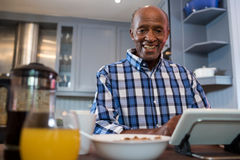 Portrait of senior man using tablet. While sitting at table in kitchen Stock Photography