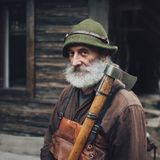 Portrait of a senior man walking in the forest. Portrait of old bearded forester with axe near wooden hut royalty free stock photography