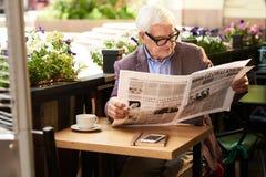Modern Senior Man Reading Newspaper Outdoors Royalty Free Stock Images