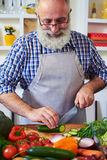 Portrait of senior man wearing gray apron cutting cucumber while. Close-up portrait of senior man wearing gray apron cutting cucumber while preparing healthy Stock Photos