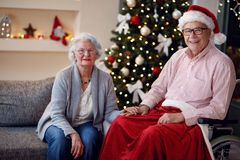 portrait of senior man in wheelchair and smiling woman with Christmas gift. royalty free stock photos
