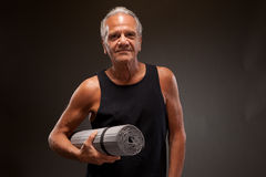 Portrait of a senior man with a yoga mat Stock Images