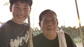 Portrait of senior man and young boy with smile face, 4K Handheld of asian boy with grand father on swing looking on camera . stock footage