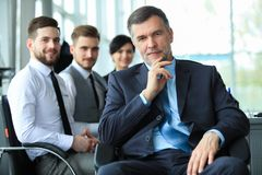 Mature smiling business manager in front of his business team royalty free stock photography