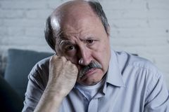 Portrait of senior mature old man on his 60s at home couch alone feeling sad and worried suffering pain and depression Royalty Free Stock Image