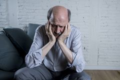 Portrait of senior mature old man on his 60s at home couch alone feeling sad and worried suffering pain and depression. In sadness face expression in retirement Royalty Free Stock Image