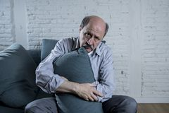 Portrait of senior mature old man on his 60s at home couch alone feeling sad and worried suffering pain and depression. In sadness face expression in retirement Stock Images