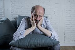 Portrait of senior mature old man on his 60s at home couch alone feeling sad and worried suffering pain and depression. In sadness face expression in retirement Stock Photo