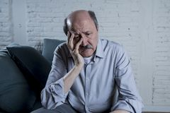 Portrait of senior mature old man on his 60s at home couch alone feeling sad and worried suffering pain and depression Royalty Free Stock Photos