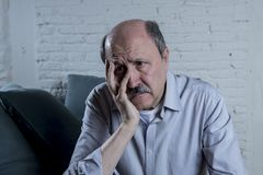 Portrait of senior mature old man on his 60s at home couch alone feeling sad and worried suffering pain and depression. In sadness face expression in retirement Stock Image