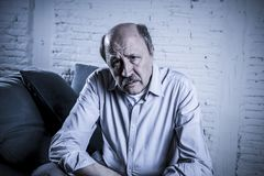 Portrait of senior mature old man on his 60s at home couch alone Stock Images