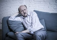 Portrait of senior mature old man on his 60s at home couch alone Stock Photo