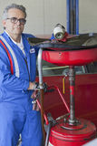 Portrait of senior mechanic standing besides car spray paint equipment Stock Photos
