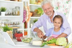 Senior man with granddaughter preparing dinner in kitchen Royalty Free Stock Photography