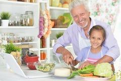 Senior man with granddaughter preparing dinner in kitchen Stock Photography