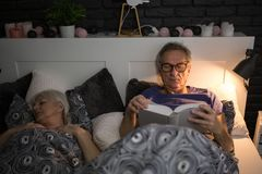 Senior man reading book in bed before sleep. Portrait of senior men reading book in bed before sleep Royalty Free Stock Photo