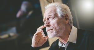 Portrait of senior modern man talking on mobile phone stock image