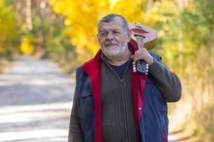Portrait of senior musician with mandolin on the shoulder standing on a country road in an autumnal forest Stock Photography