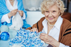Portrait of senior needlewoman. Portrait of pretty blond-haired senior women looking at camera with deep black eyes while holding unfinished knitted scarf and Royalty Free Stock Image