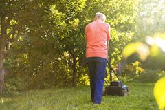 Portrait of senior old man using lawn mower in the garden on summer day royalty free stock images